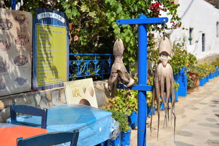 SIFNOS, GREECE - September 18, 2018: Drying octopus on the street near the restaurant. Sifnos island, Cyclades, Greece.