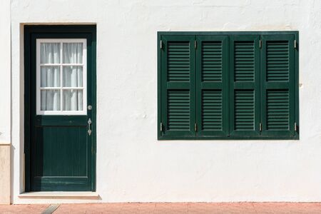 Traditional Spanish architecture with white facade and green doors and windows. Menorca, Spain 版權商用圖片