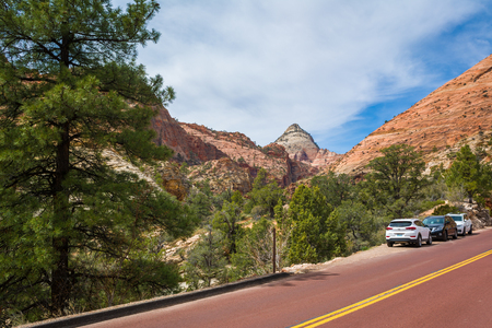 Utah, USA - April 7,2019: Road through the Zion National Park. Landscape of rock hills and trees. Utah, USA