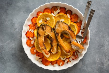 Fried carp fish slices with carrot and oranges. Traditional Polish Christmas eve dish.