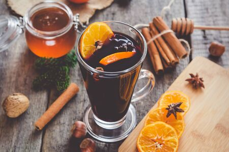 Hot mulled wine with orange, cinnamon, honey and anise on wooden background. Stok Fotoğraf