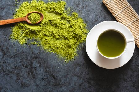 Green tea matcha in a white cup. Flat lay. Dark background