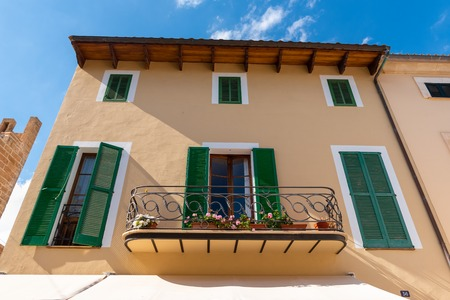 Mallorca, Spain - May 10,2019: Typical Spanish house with green shutters in Alcudia Old Town