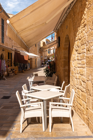 Mallorca, Spain - May 10,2019: Tables and chairs in cafe on street in Alcudia Old Town, Mallorca
