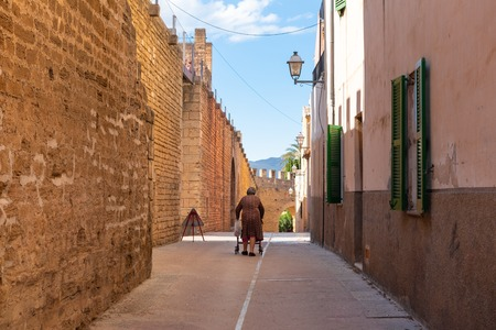Mallorca, Spain - May 10,2019: Elderly woman on street in Alcudia Old Town in Majorca. Redakční