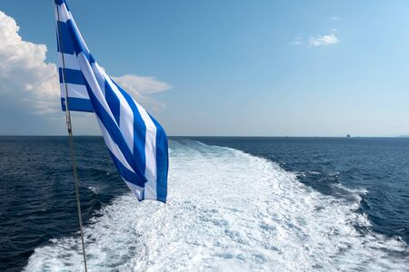 Greek flag and water trail foaming behind a ferry boat in Aegean Sea. Greece.