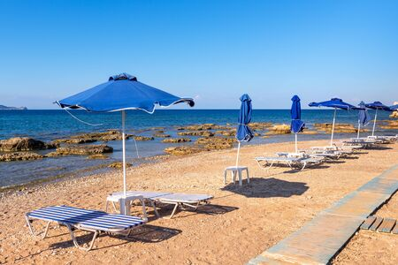 Sun loungers with umbrella on beautiful Kolymbia beach. Rhodes island, Greece