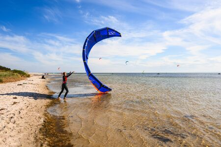 Jastarnia, Poland, May 9, 2020: A young man kitesurfer ready for kite surfing rides in sea
