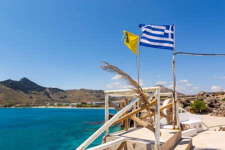 Greek flag on terrace overlooking blue sea. Kolymbia on Rhodes island. Greece Standard-Bild