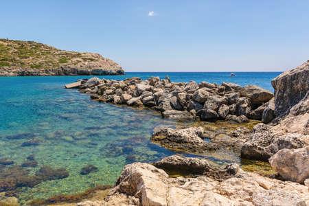 Rocky coast of Kolymbia bay in sunny day. Rhodes island, Greece Standard-Bild