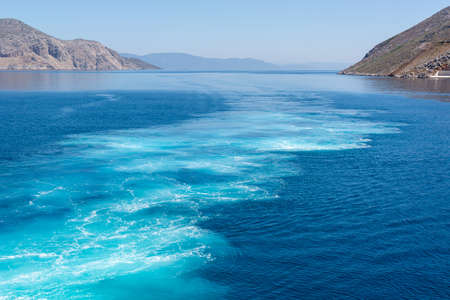 Water trail foaming behind a ferry boat. Cyclades, Greece.