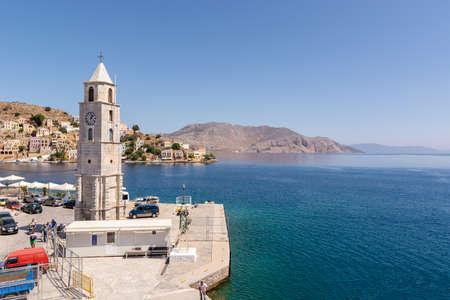SYMI, GREECE - May 15, 2018: Clock tower Symi and sea bay on Symi island, Greece