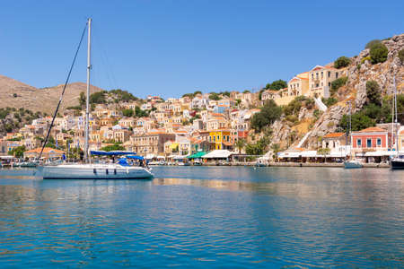 The beautiful island of Symi with a turquoise bay and colorful architecture Dodecanese, Greece Standard-Bild