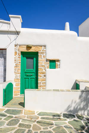 Building with green doors on whitewashed street in beautiful Chora town on Folegandros Island, Cyclades, Greece. Editorial
