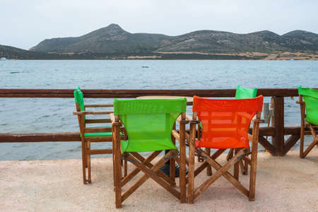 Tables with colorful chairs in Greek seaside restaurant on Antiparos island. Cyclades, Greece 免版税图像