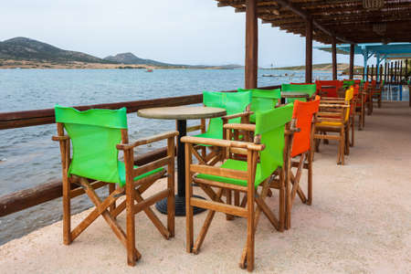 Antiparos, Greece - September 28, 2021: Tables and chairs in Greek seaside restaurant on Antiparos island. Cyclades, Greece 免版税图像