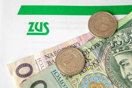 Gdansk, Poland - April 17, 2021: ZUS (National Social Insurance Company) logo on a sheet of paper and polish money 新闻类图片