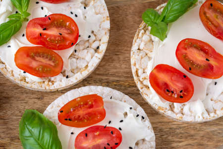 Rice cake sandwich with cheese cream, tomato, basil and spices. A healthy dietary snack Standard-Bild