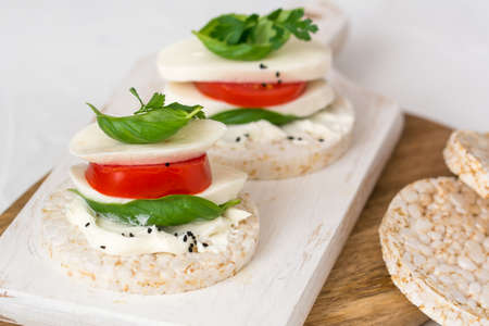 Rice cake sandwich with cheese cream, mozzarella, tomato, basil and spices. A healthy dietary snack 免版税图像