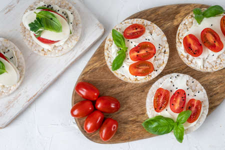 Rice cake sandwich with cheese cream, tomato, basil and spices. A healthy dietary snack 免版税图像