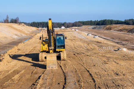 Excavator on a highway construction site. Road construction work