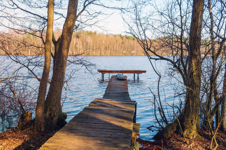 Old wooden jetty on the lake in early spring. Kashubia in Poland