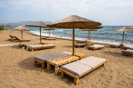 Sun beds and umbrellas at Soros beach on Antiparos Island. A wonderful beach with the golden sand and azure waters. Cyclades, Greece 免版税图像