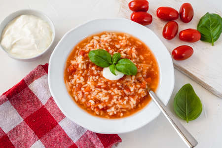 Tomato soup with rice decorated by cream and basil leaf.