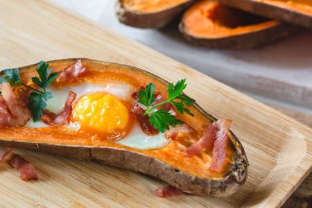 Baked sweet potato with fried egg, bacon and parsley. 免版税图像