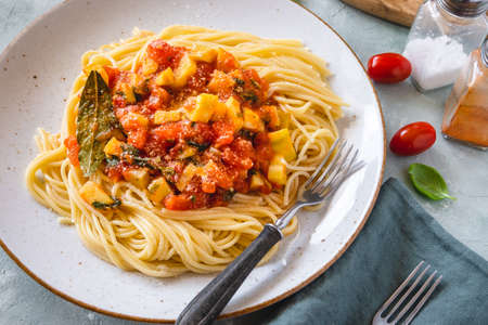 Pasta with zucchini, tomato sauce and grated cheese