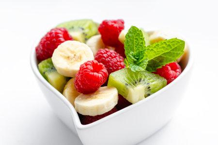 Healthy fresh fruit salad in bowl on white background 免版税图像