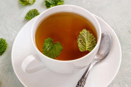 Fresh lemon balm tea in a white cup.