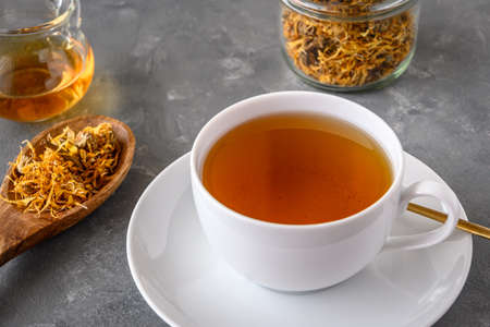 Calendula tea in a white cup. Herbal tea with dried marigold flowers.