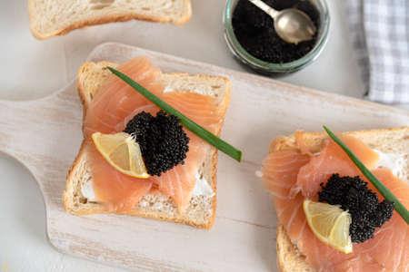 Appetizer toast bread with creamy cheese, salmon and black caviar. Standard-Bild
