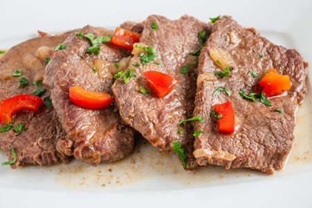 Braised beef cooked with red pepper, served on a plate