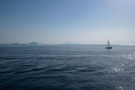 aeolian: BOAT ON THE SHINING SEA WITH AEOLIAN ISLANDS IN THE BACKGROUND Stock Photo