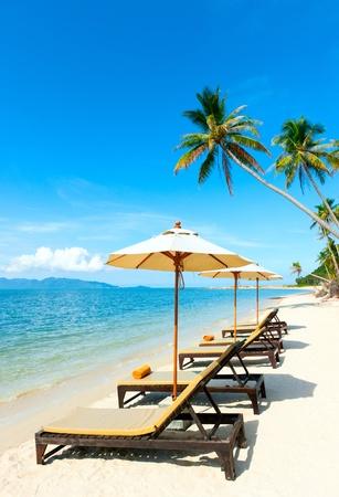 Stoelen met parasol op het strand in de buurt met uitzicht op zee
