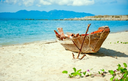 fisherman boat: Old fisherman boat with anchor on the sea beach