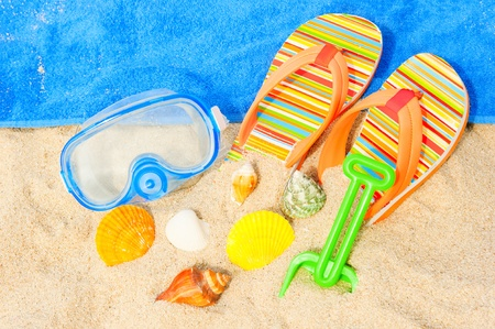 Seashells, diving mask and sandals on the beach photo