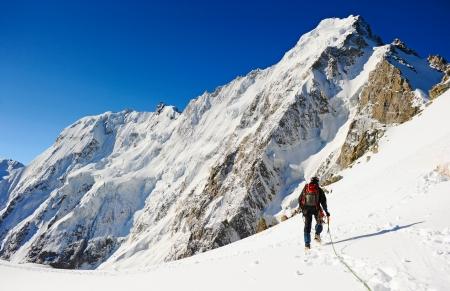 klimmer: Bergbeklimmer sport Een klimmer het bereiken van de top van de berg