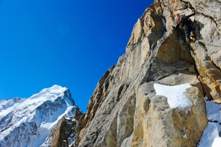Mountaineer sport  A climber reaching the summit of the mountain photo