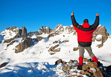 Male mountain climber raising hands on top photo
