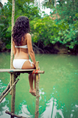 Beautiful lonely girl sitting on the river dock photo
