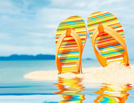 Beach sandals on the sandy sea coast Imagens