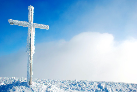 Cross on the top of the mountain in winter