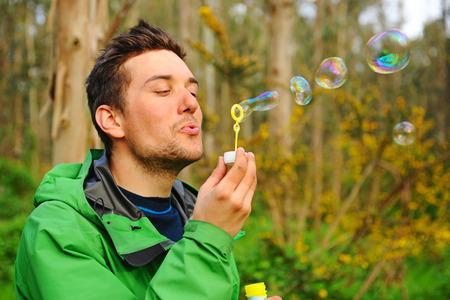 blowing bubbles: Man blowing bubbles outdoor