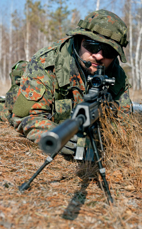 special service: Masked sniper is aiming at the target during the mission
