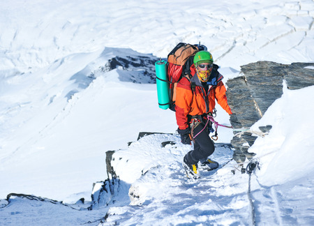 mountaineer: Mountaineer reaches the top of a snowy mountain Stock Photo