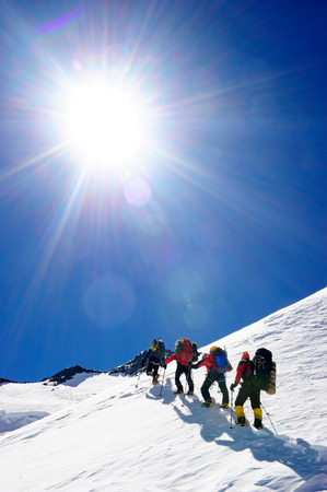 Group of mountain backpackers walking on snow