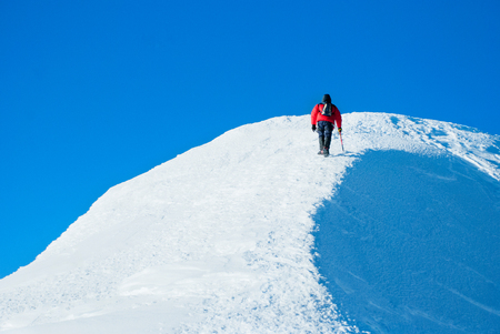 top mountain: A lonely climber reaching the summit Stock Photo